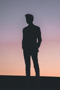 silhouette noir contre jour d'un homme debout tombée de la nuit
