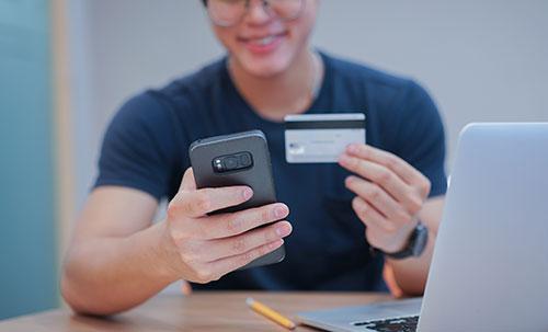 homme avec un smartphone et une carte de credit